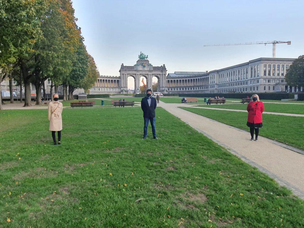 Kuvassa kolme henkilöä maskit naamalla seisovat turvavälein isossa puistossa.