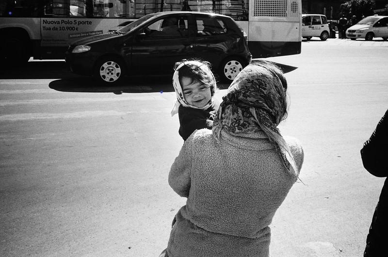 Nainen kantaa nauravaa lasta Italian Palermossa.