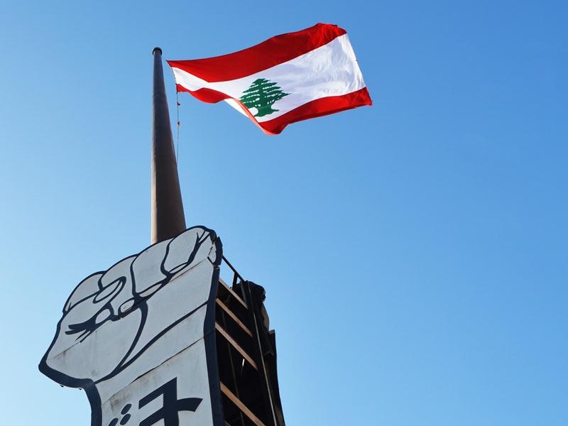 Libanonin lippu liehuu nyrkkiä esittävän patsaan päällä.
