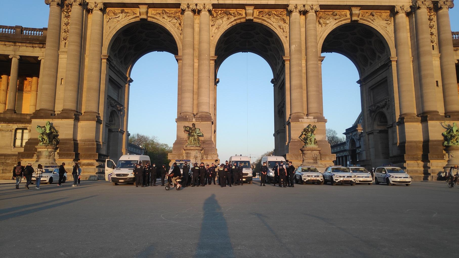 Kymmenkunta poliisiautoa ja niiden poliisipartiot seisovat rivissä Brysselin suuren Cinquentanaire-puiston kaari-monumentin edessä.