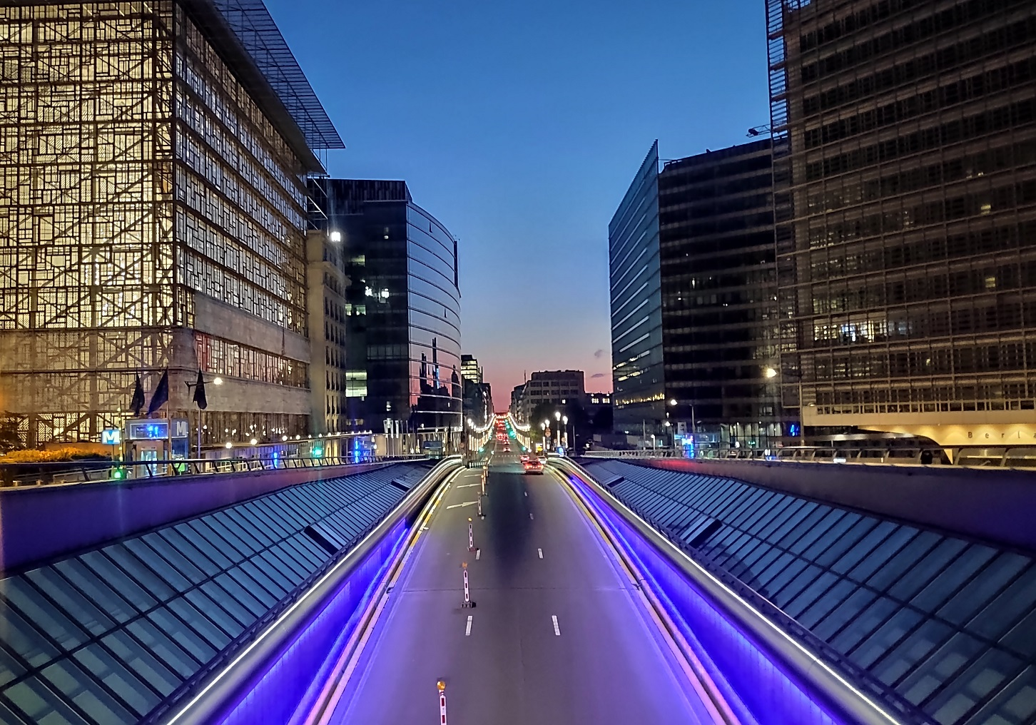 Öisessä sinertävässä näkymässä keskellä autotie, jonka molemmin puolin kohoaa EU-instituutioiden rakennuksia.