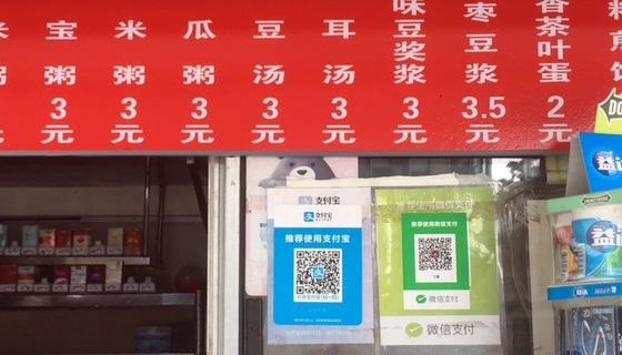 Paikallinen kioski, jonka ikkunassa lapuissa kehotetaan käyttämään mobiilimaksua asioimiseen.