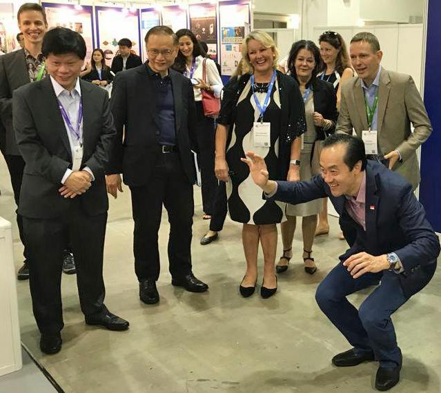 Apulaisministeri Koh Poh Koon Singaporen kauppa- ja teollisuusministeriöstä testasi suomalaisen Rehaboo!'n kuntoilupeliä TechInnovation-tapahtumassa. Kuva: Paula Kivistö.
