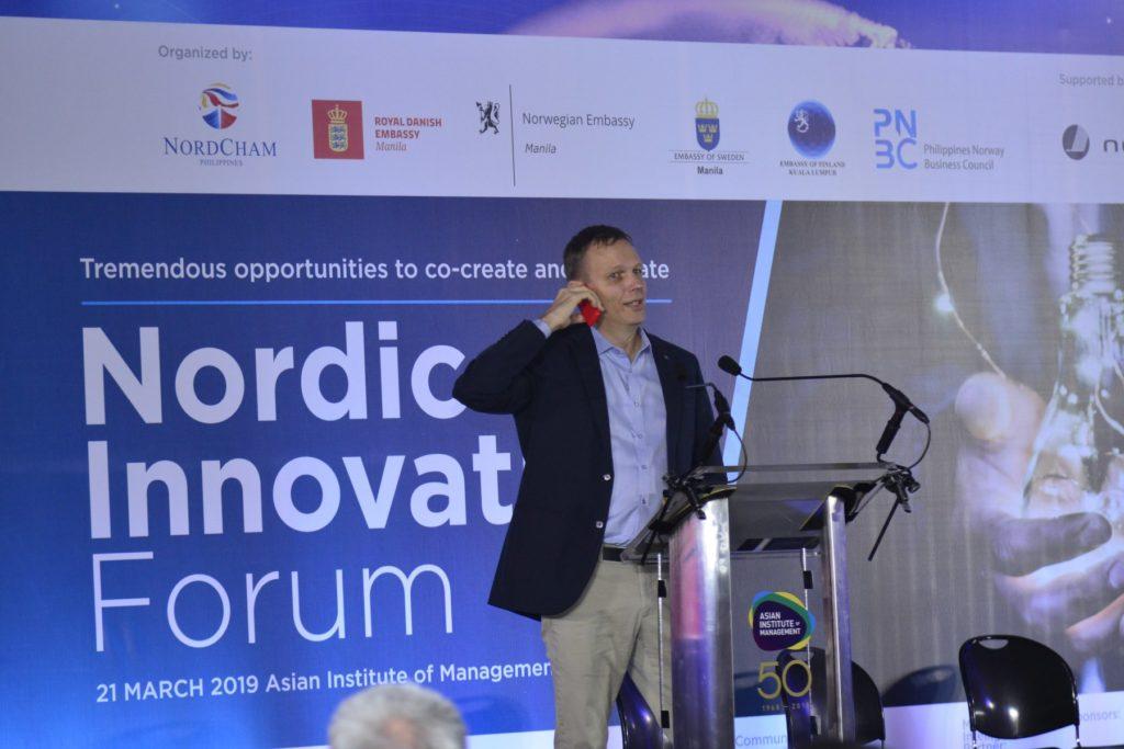 Suomen Singaporen-suurlähetystön Riku Mäkelä esitteli Nokian puhelin korvallaan Singaporeen perustettua Nordic House -innovaatiohautomoa. Kuva: Nordcham Philippines.