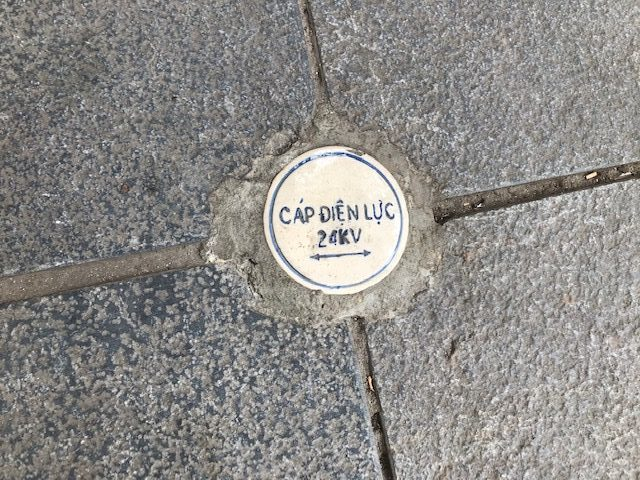Cap Dien Luc; posliininen merkki jalkakäytävässä kertoo sähköjohtojen sijainnin ja viemärin sekä vesijohdon suunnan. Hanoin vesiprojekti on tunnetuin, suurin ja arvostetuin suomalaishanke Vietnamissa. Kuva: Kari Kahiluoto