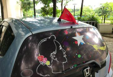 Aung San Suu Kyin kuvat ja NLD:n liput koristavat autoja ja Yangonin katukuvaa