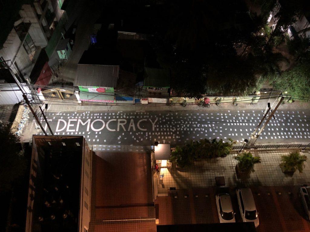 """Kuvassa katu kuvattuna ylhäältä ja kadussa teksti """"demokratia"""""""
