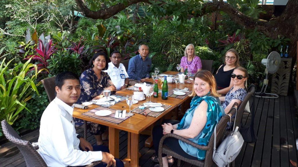 Kuvassa lähetystön henkilökuntaa ulkona pöydän ääressä