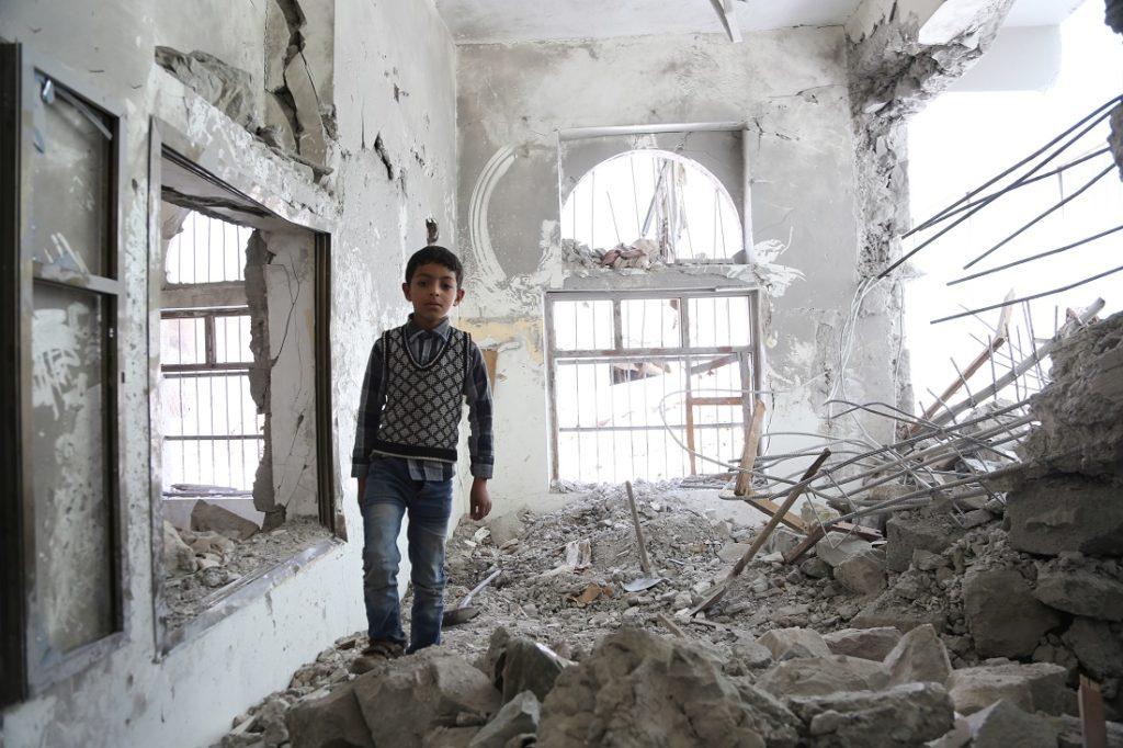 Kuvassa 6-vuotias Ali seisoo kotitalonsa raunioissa Jemenin pääkaupungissa Sanaassa vuonna 2015.