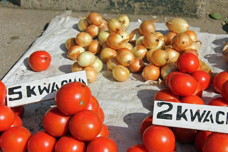 Tomaatteja ja sipuleita myyntialustalla maassa.