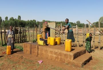 Nainen pumppaa käsikaivolla vettä keltaiseen isoon kanisteriin. Nuori tyttö kantaa selässää kanisteria. Yksi nainen seisoo kuvan reunassa.