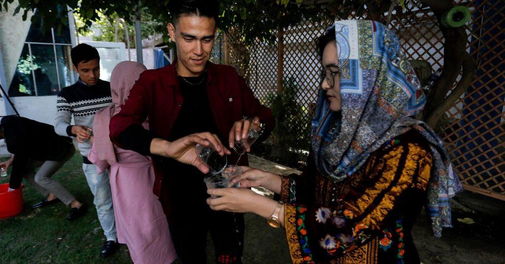 Alyas Rahimi ja Faradis Farhat osallistuivat Kabulissa järjestettyyn työpajaan. Kuvassa nuoret muodostavat pihalla ketjun, jossa osallistujat kuljettavat vettä laseista laseihin. Kuva: Ango