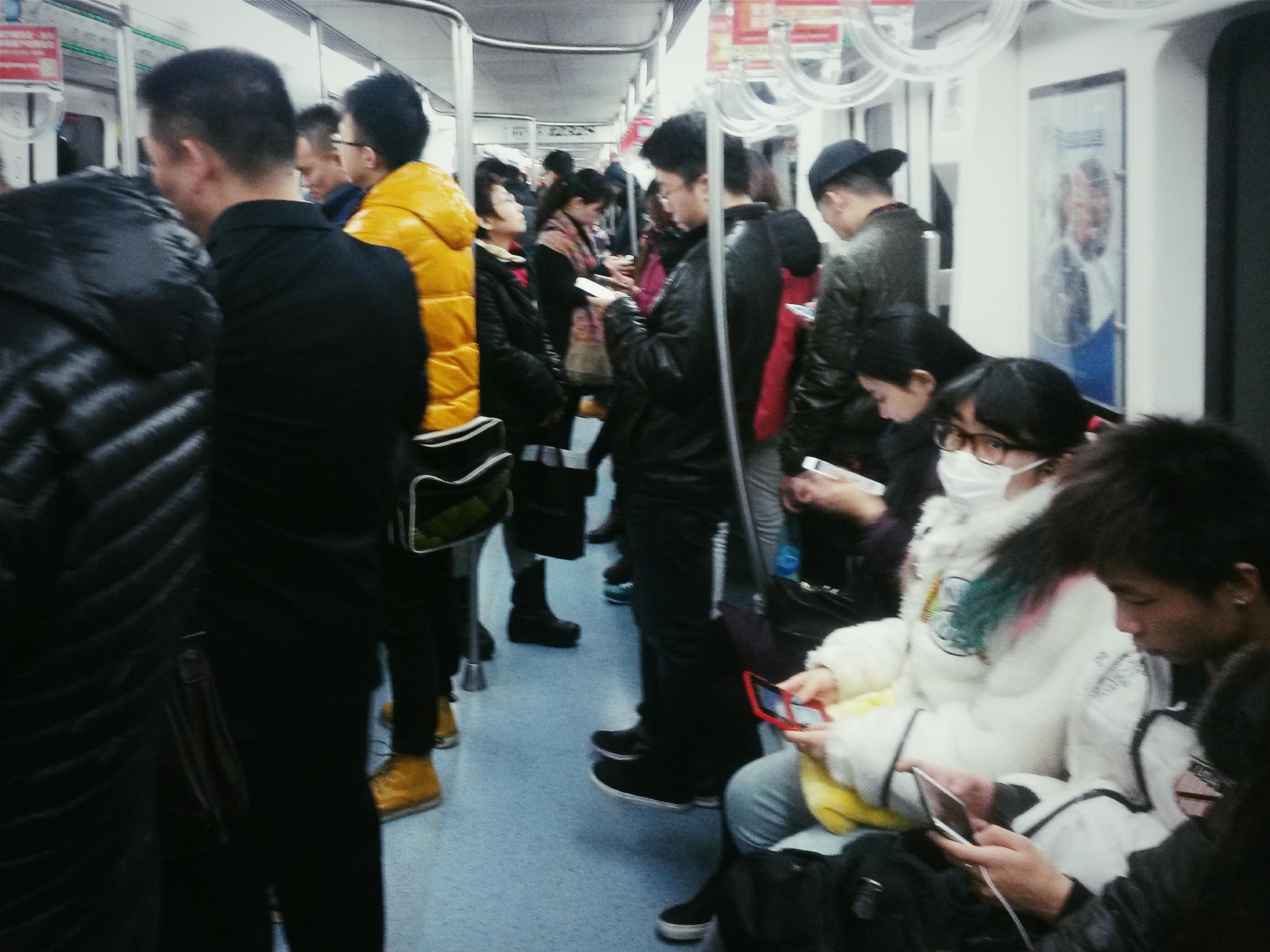 Pekingin metrossa älypuhelimet piippaavaat taajaan, kun matkustajat selaavat somekanaviaan. Kuva: Heta Hassinen