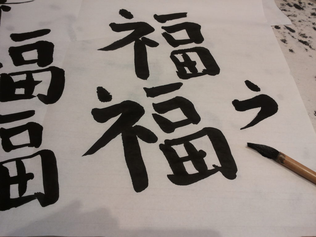 Sivellinotteeni jälkeä kalligrafiatunnin päätteeksi lokakuulta 2013. Kuten kuvasta näkyy, olisin saattanut kaivata lisää oppitunteja. Kuvan grafiikka yrittää jäljitellä kiinalaista onnea kuvaavaa merkkiä fu. Kuva: Anu Kerttula.