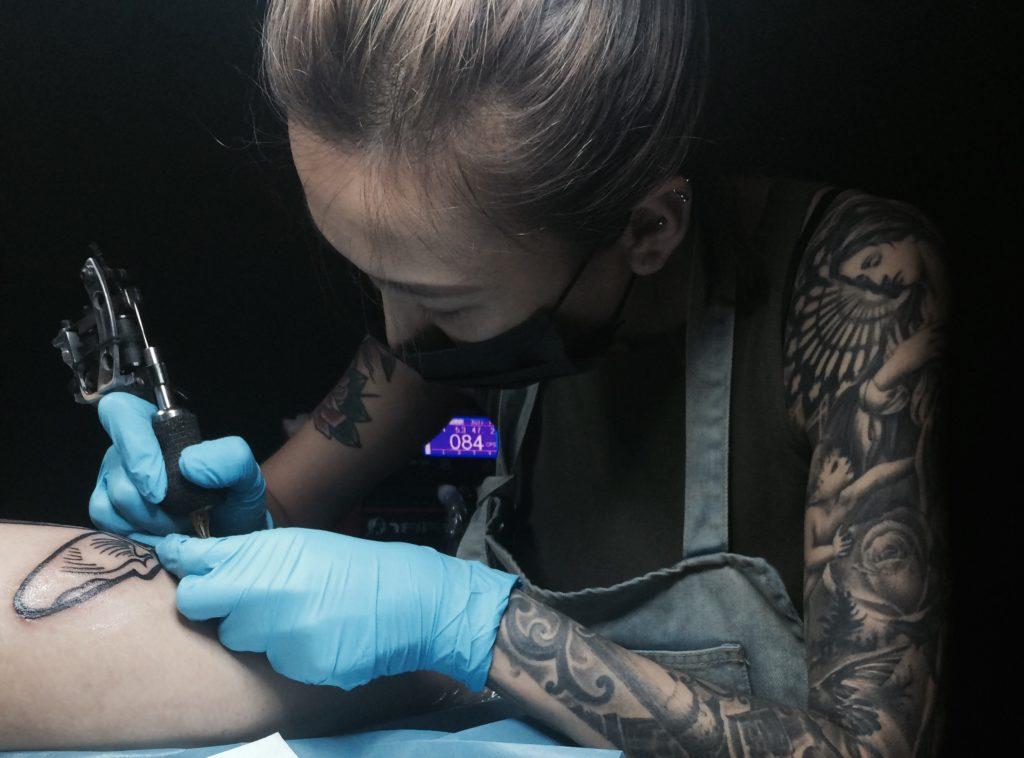 413 Tattoo -liikkeen omistava Candice työn ääressä. Kuva: Xie Yishan.