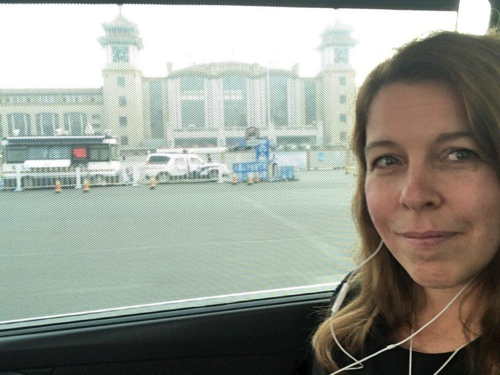 Raportoija perehtyy seuraavaan aiheeseen matkalla tapaamiseen. Taustalla Pekingin rautatieasema. Kuva: Emmi Oikari.