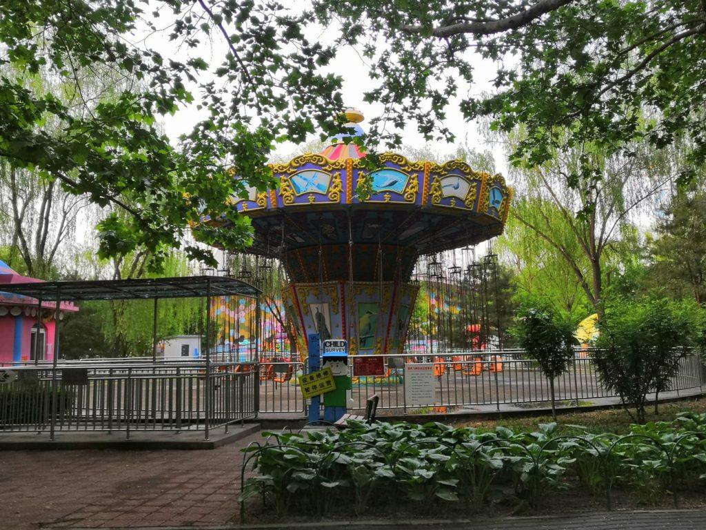 Chaoyangin puiston kasvillisuuden seasta paljastuu värikkäitä huvipuistolaitteita. Kuva: Vivian Tuominen.
