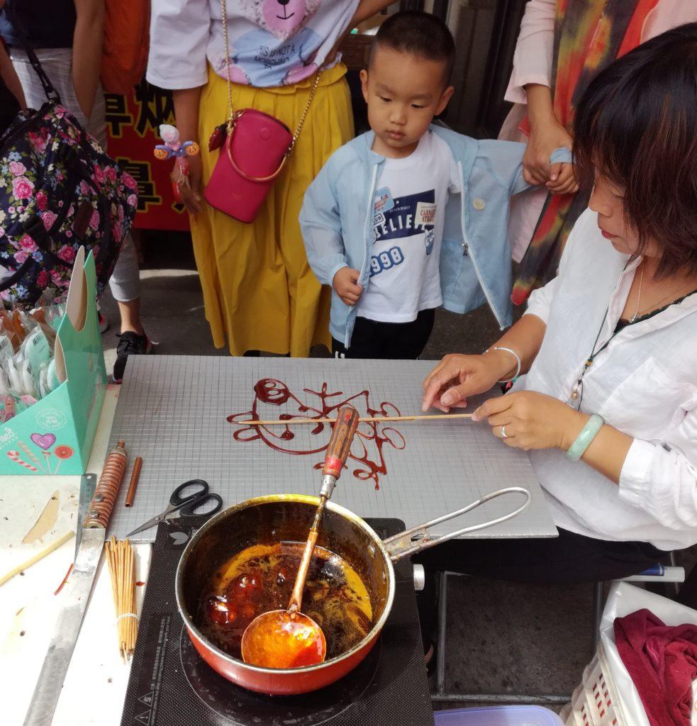 Lapsi katselee karamellin valmistusta Tianjinin kaupungissa. Kuva: Jussi Kastepohja.