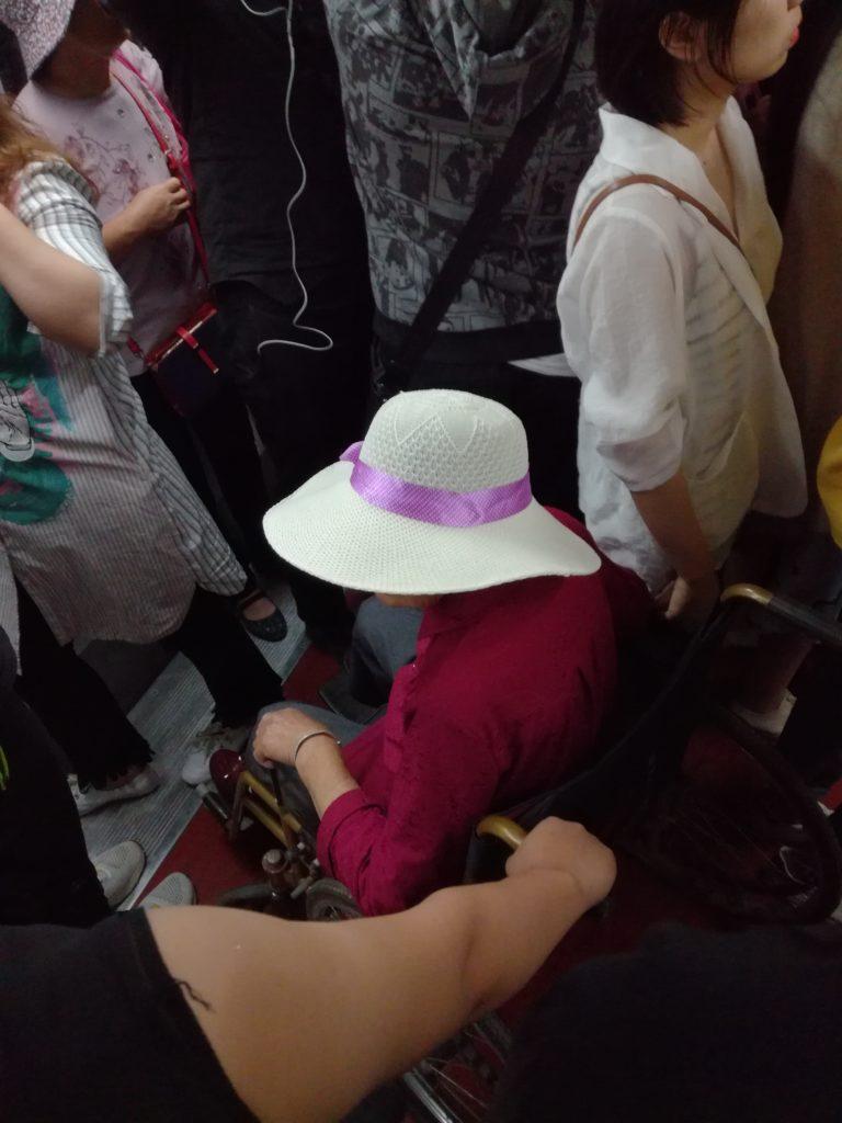 Kiinalainen nainen pyörätuolissa Pekingin aamuruuhkassa. Kuva: Jussi Kastepohja