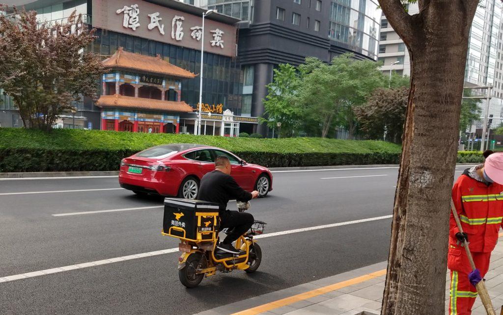 Ruokalähettien sähköskootterit ovat osa laajempaa liikenteen sähköistymisen megatrendiä, ja niiden ohella esimerkiksi kuvassa näkyvä sähköauto Tesla on yleinen näky Pekingin liikekeskustassa. Kuva: Petja Karppinen.