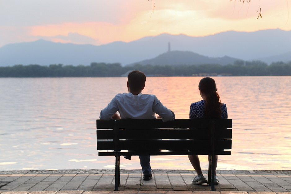 Mies ja nainen penkillä selin kuvaajaan. Taustalla auringonlasku.