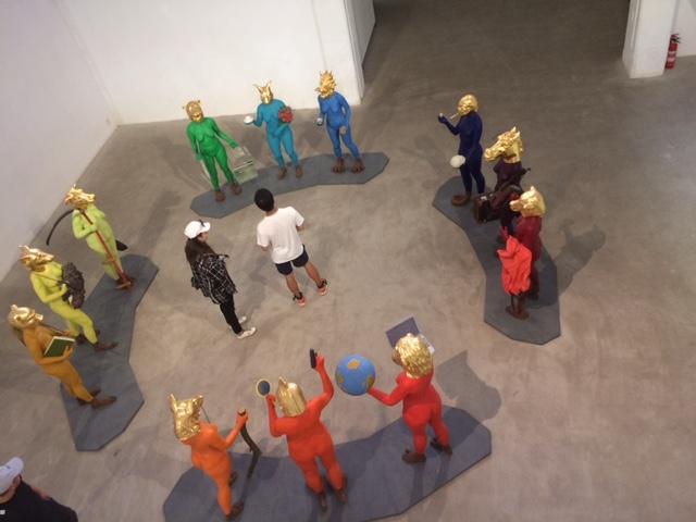 Rinki 12:sta täysikokoisista hahmosta, joilla om kädesään eroolejaan kuvailevia tavaroita kuten kirja. Päät ovat eläinten. Ringin keskellä kaksi museokävijää.