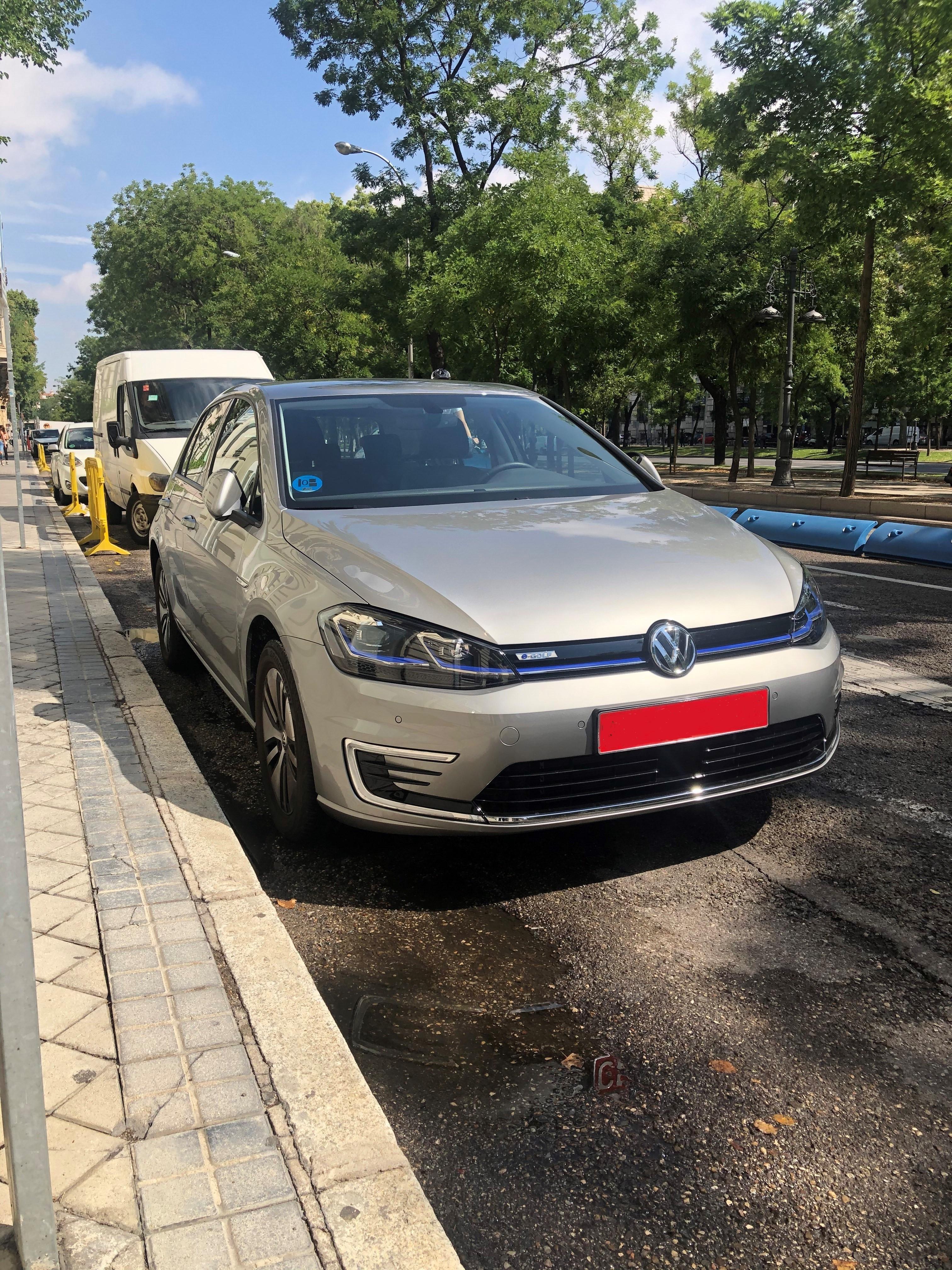 Harmaa Volgswagen-merkkinen sähköauto parkkeerattuna kadulle.