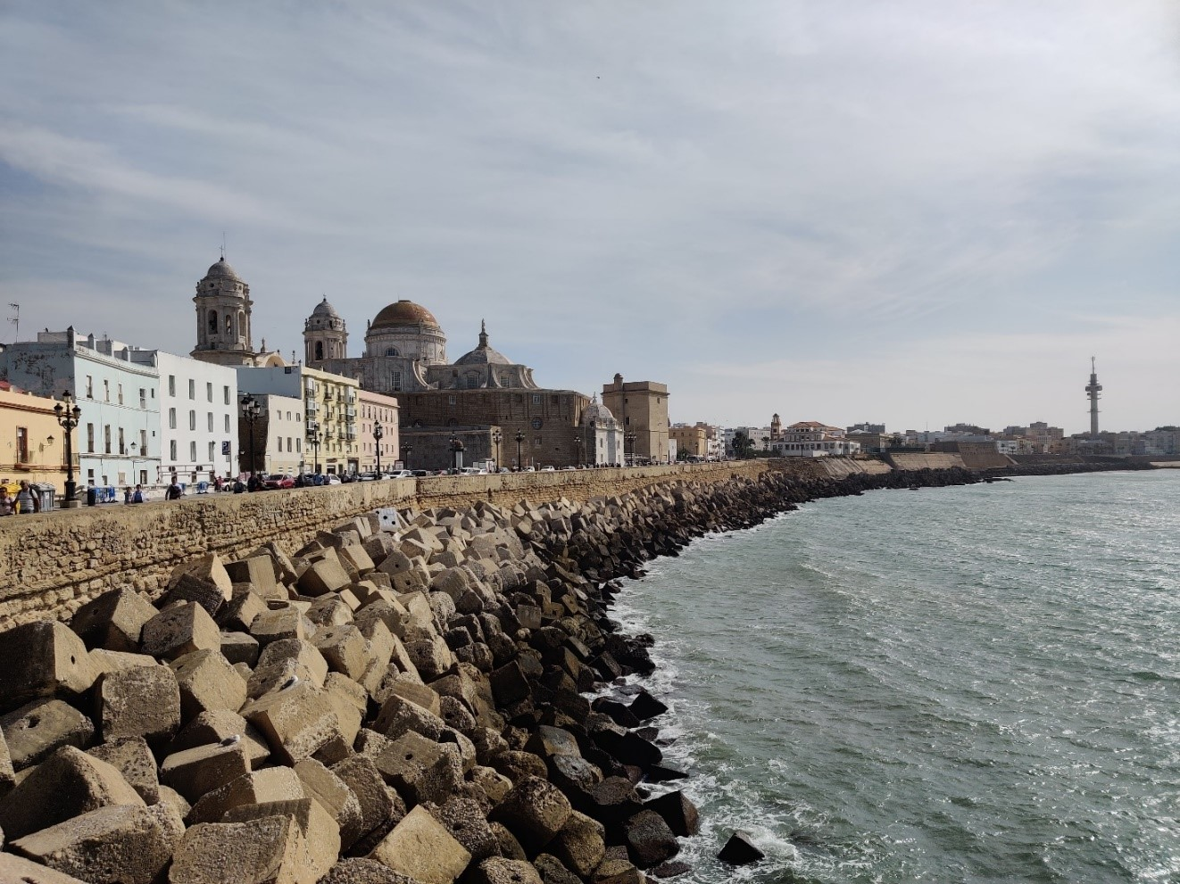 Kuvassa näkyy Cádizin rantaviivaa. Vasemmalla taloja ja suuri katedraali. Oikealla valtameri, jonka aallot osuvat rantavalliin