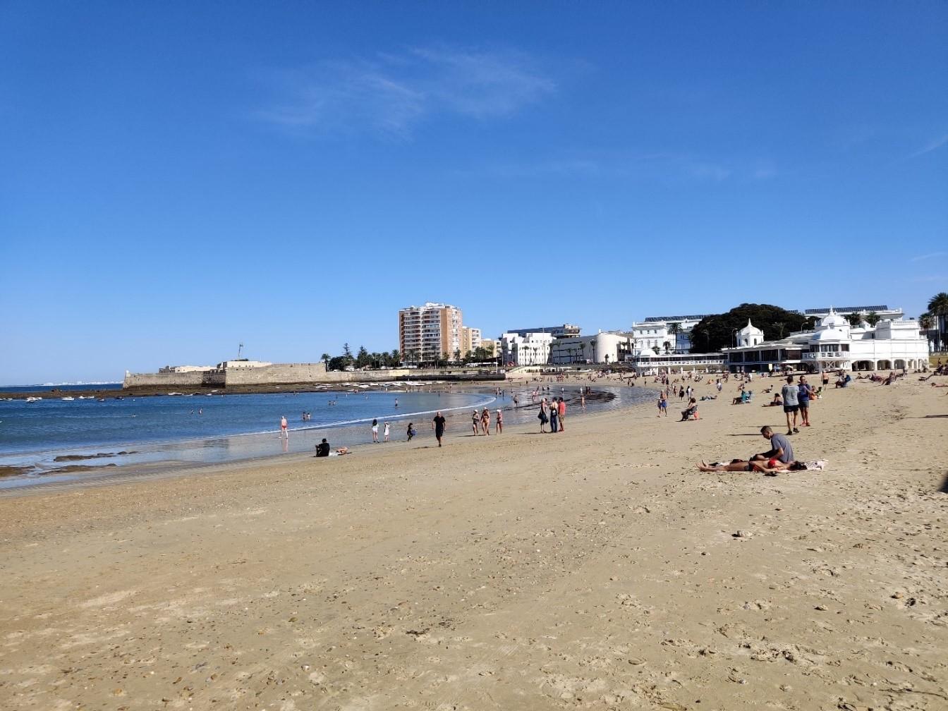 Uimaranta. Vasemmalla merta, oikealla hiekkaranta ja ihmisiä sekä valkoinen rantamökki.