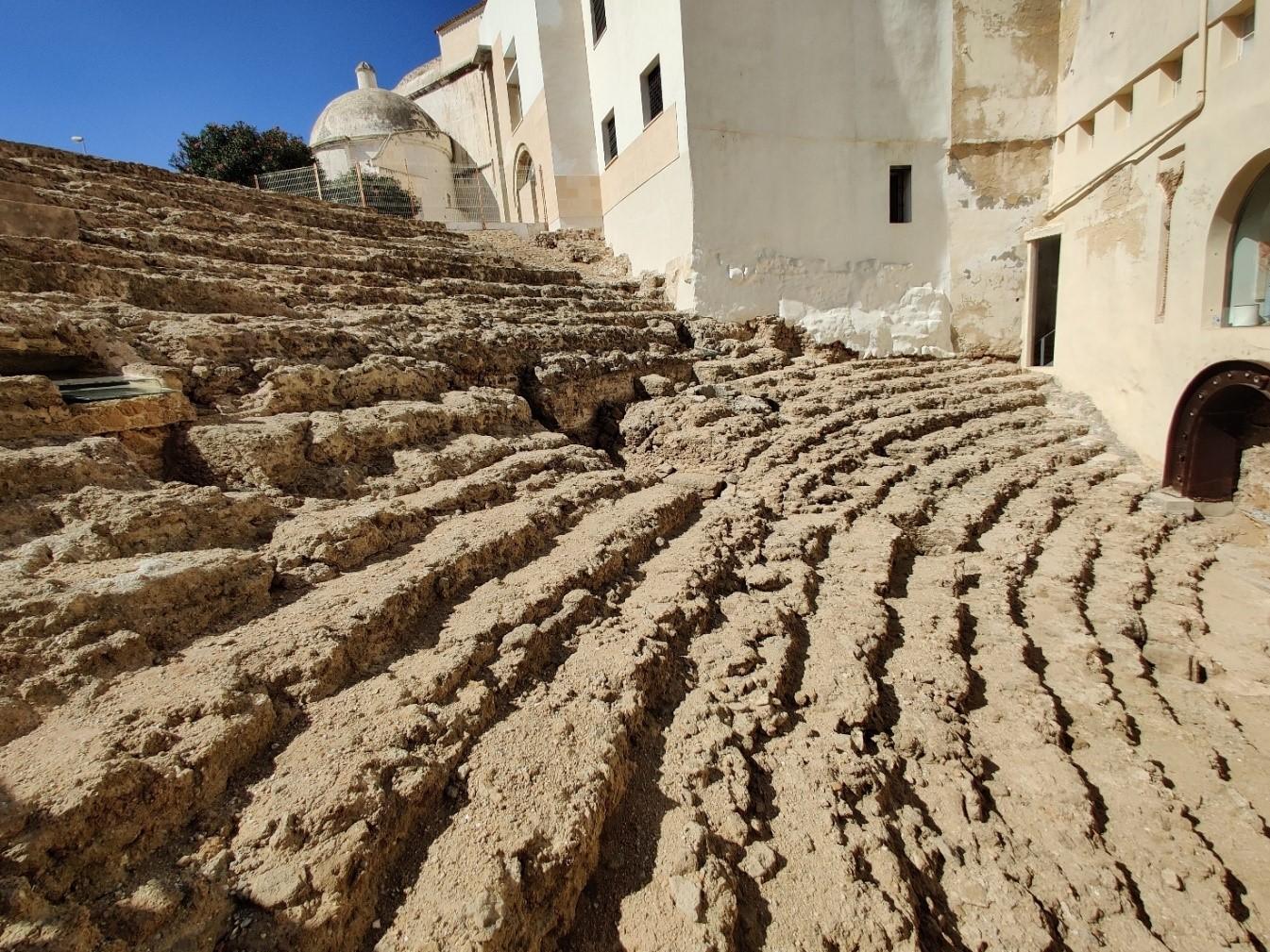 Vanha raunioitunut amfiteatteri. Kuvassa näkyy teatterin rappeutuneita penkkirivejä.