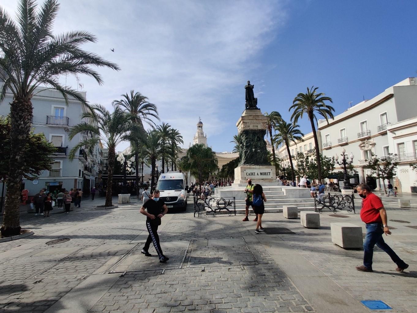 Aukio, jonka keskellä iso ihmistä muistuttava patsas. Ympärillä muutamia ihmisiä. Aukion laidalla palmupuita ja rakennuksia.