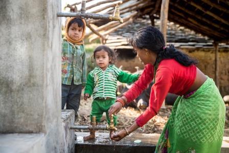 Saraswoti Dewi Dhami pesee lastensa käsiä ennen ruokailua Dotin piirikunnassa, Nepalin Kaukolännessä. Kuva: Tuukka Ervasti/UM