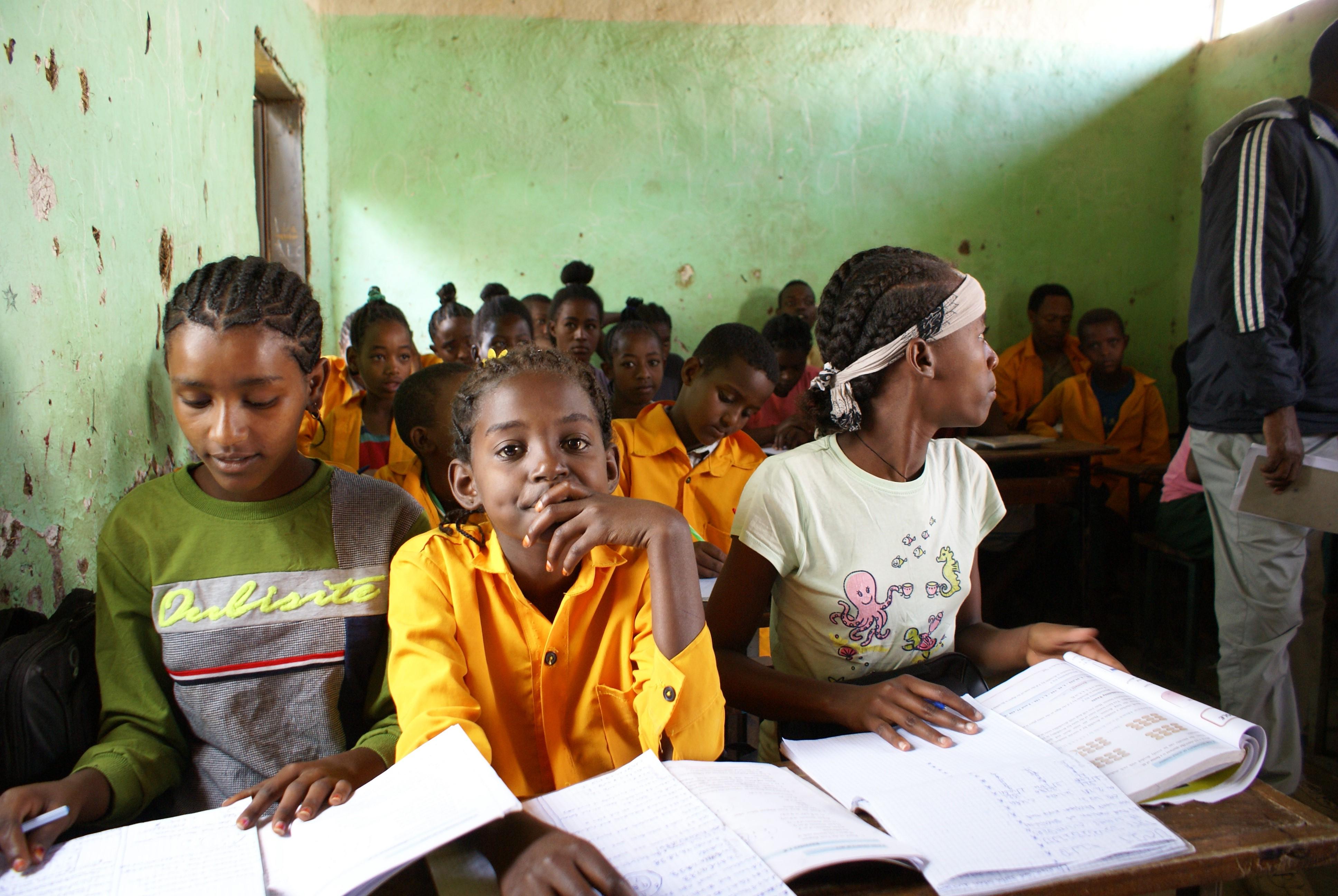 Kuvassa kolme koululaista. Vain puolet koulunsa aloittavista tytöistä saavuttaa viidennen luokan. Suurin syy koulupudokkuuteen on köyhyys. Mitä pidemmälle nämä kuudennen luokan tytöt pystyvät sinnittelemään koulussa, sitä todennäköisemmin he myös etenevät yläkouluun. Kuva: Leo Pekkala.