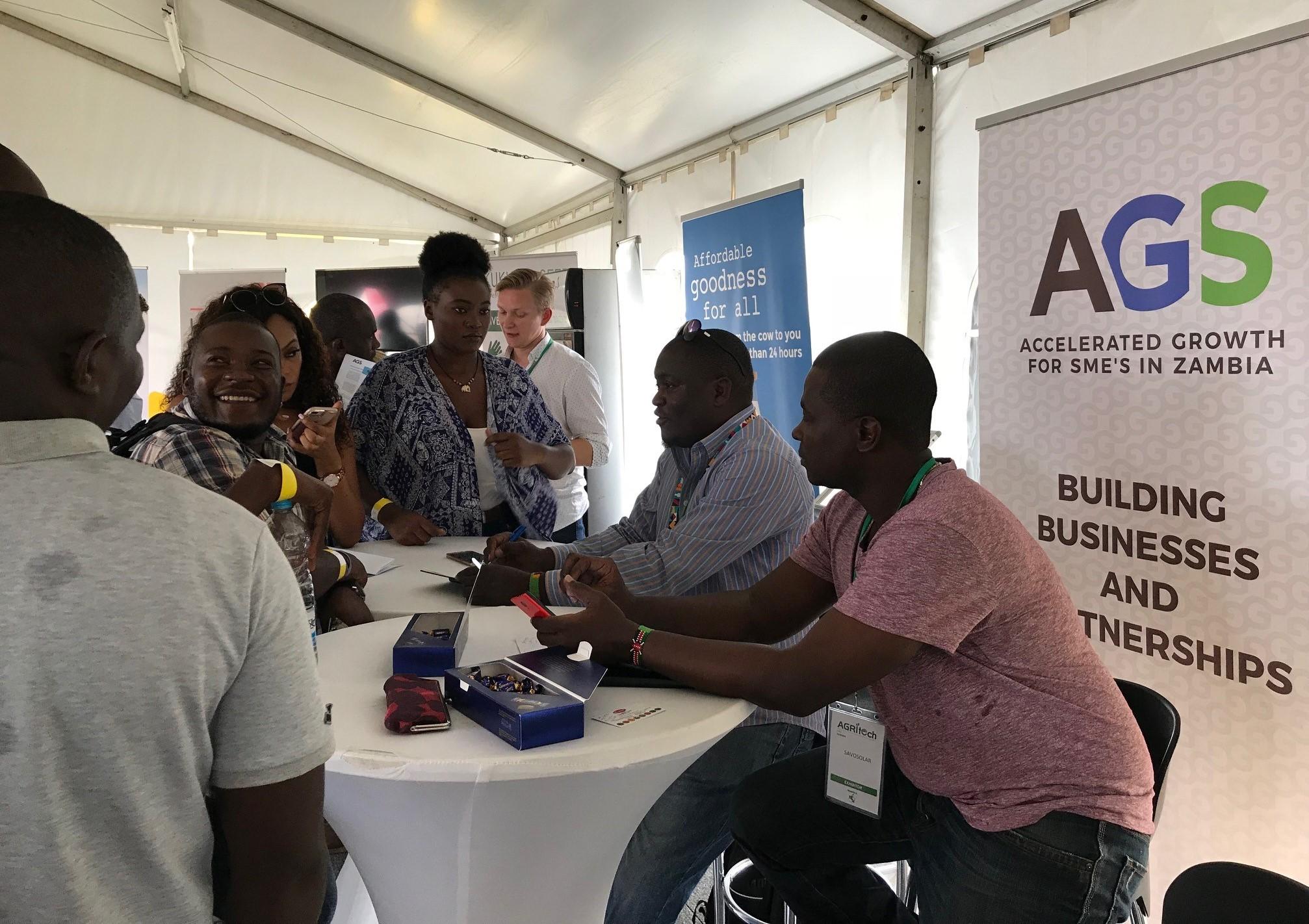 Verkostoitumista viime vuoden Agritech Expo -messuilla. Kuvassa on messuosasto ja messuvieraita esittelypöydän ääressä. Kuva: Pirjo Suomela-Chowdhury.