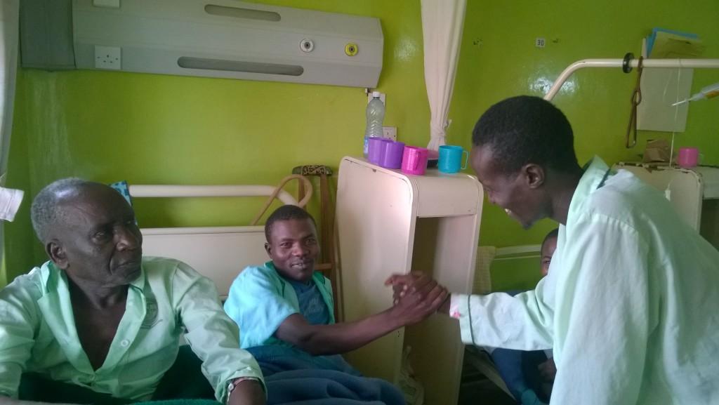 Turkana Etsua ja pokotti Abram tervehtivät sairasvuoteella, pokotti Sangura katsoo vieressä. Kuva: Kimmo Kiljunen