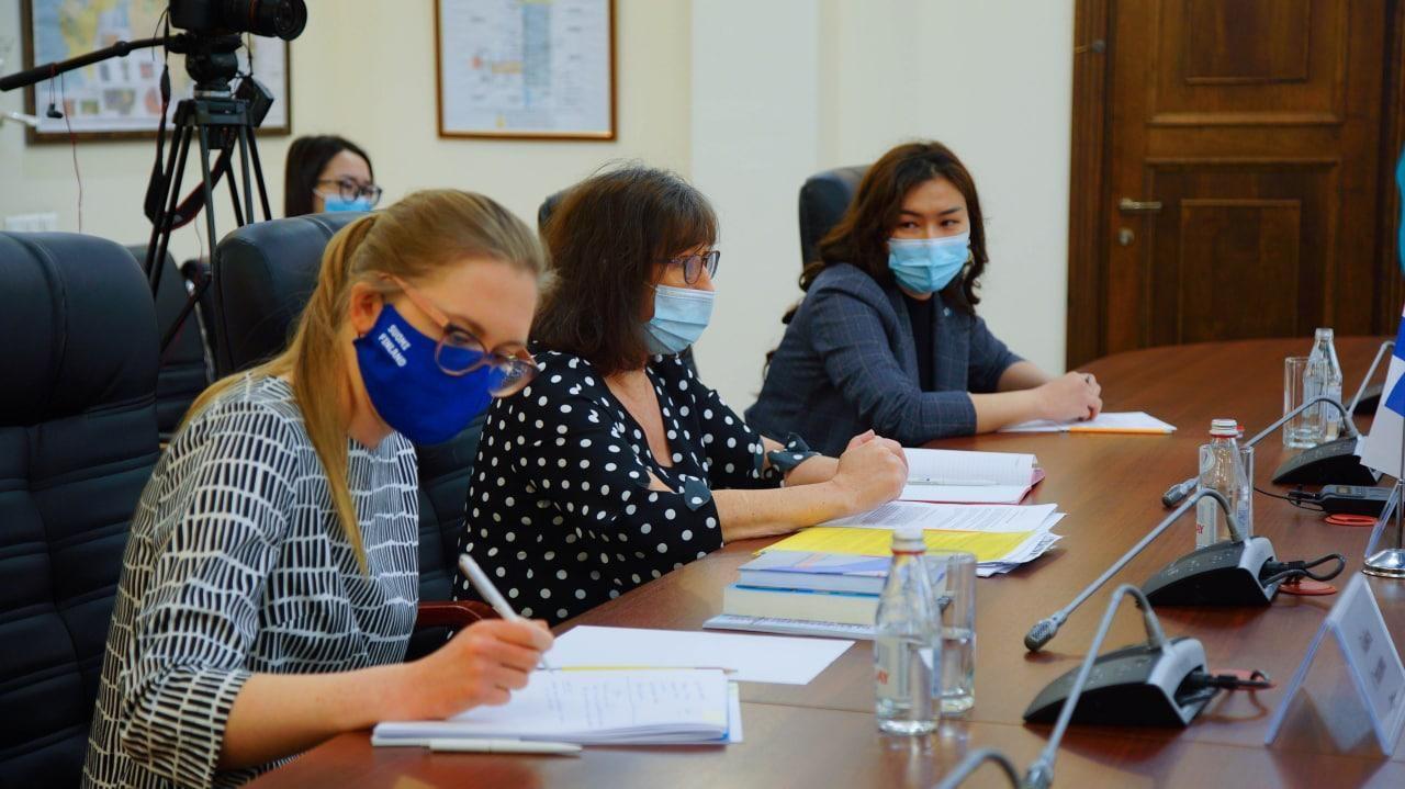Kolme naista neuvottelupöydän ääressä