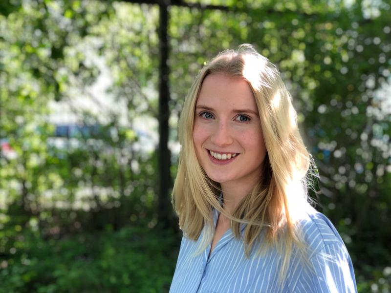 Vaalea nuori nainen seisoo tuomien katveessa ja hymyilee kameraan.