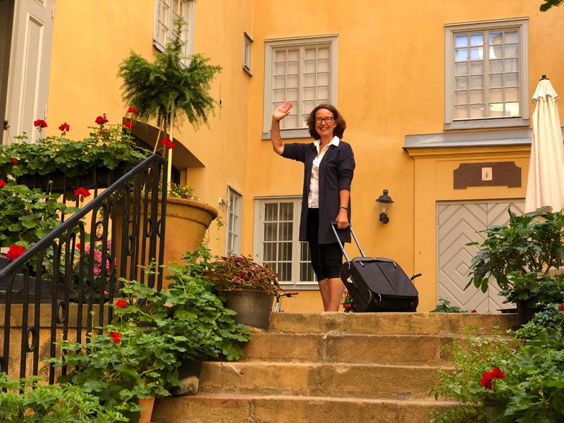 Liisa Talonpoika står på residensets innergård med sin resväska och vinkar till adjö.