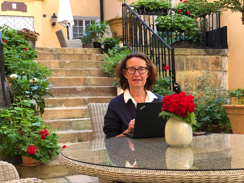Liisa Talonpoika istuu residenssin sisäpihalla pöydän ääressä tietokone edessään. Pöydällä ja ruukuissa kukkia ja taustalla ylätasanteelle vievät kiviportaat.