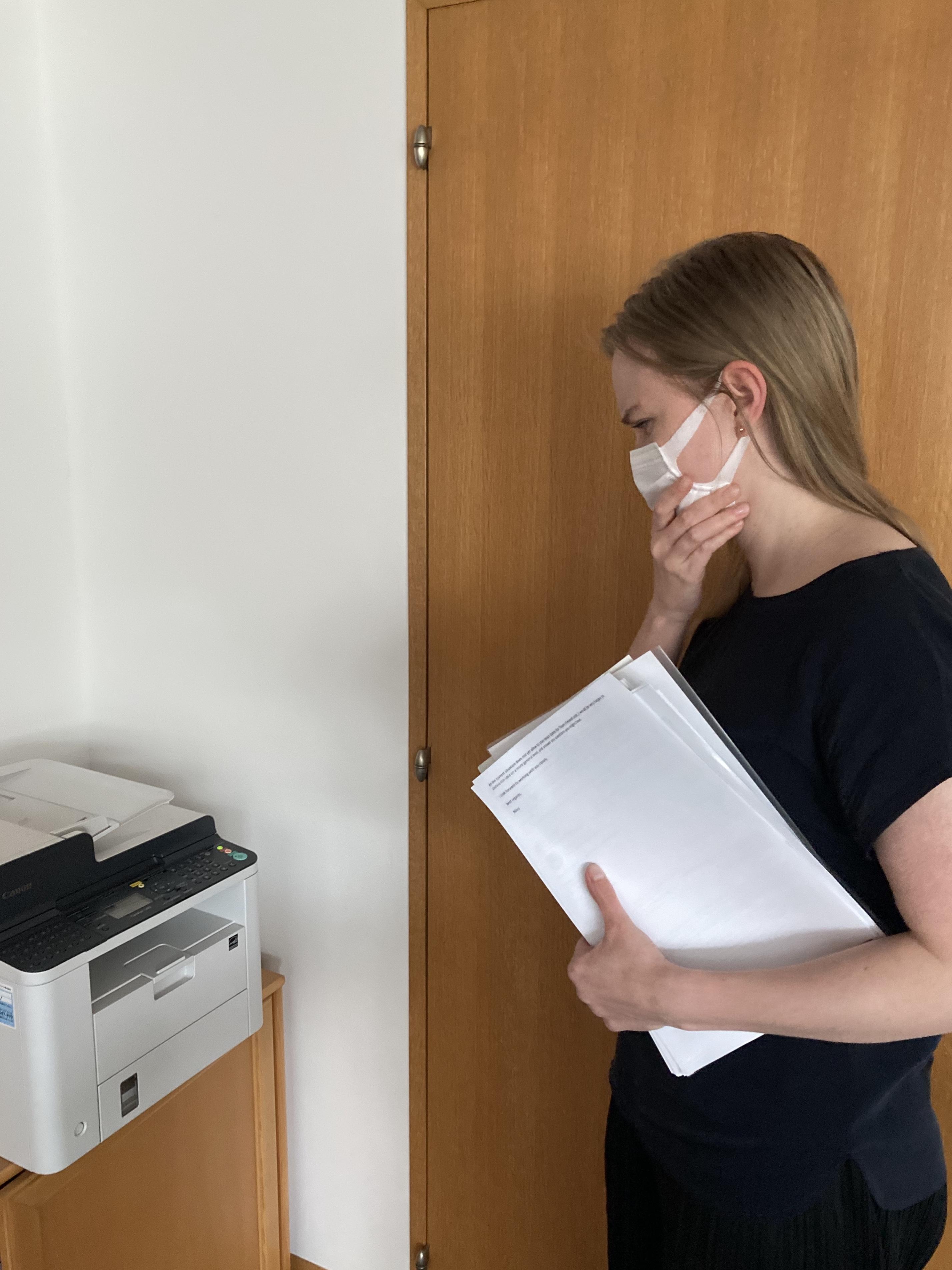 Kirjoittaja ihmettelee faksilaitetta paperipino kädessään.