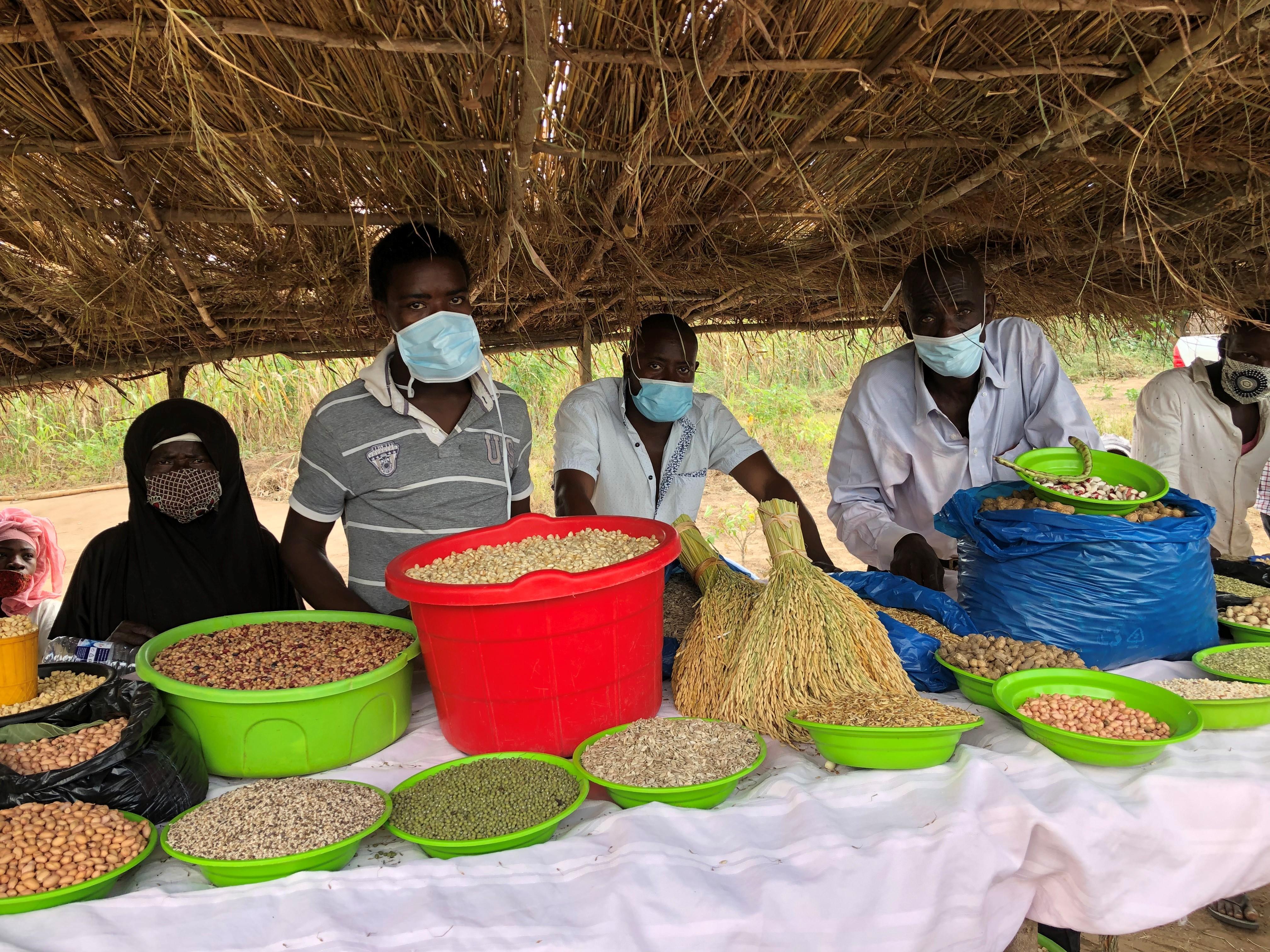 Miehiä myymässä torilla maataloustuotteita