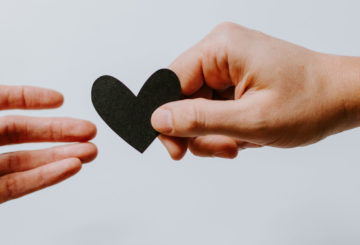 Kaksi kättä, toinen ojentaa sydämen toiselle