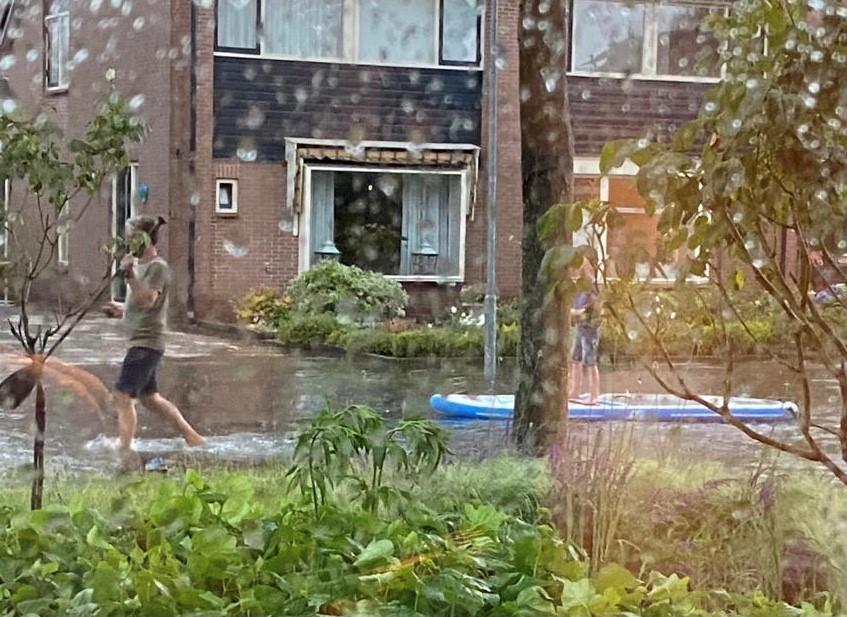 Mies kävelee ja toinen suppailee tulvivalla kadulla.