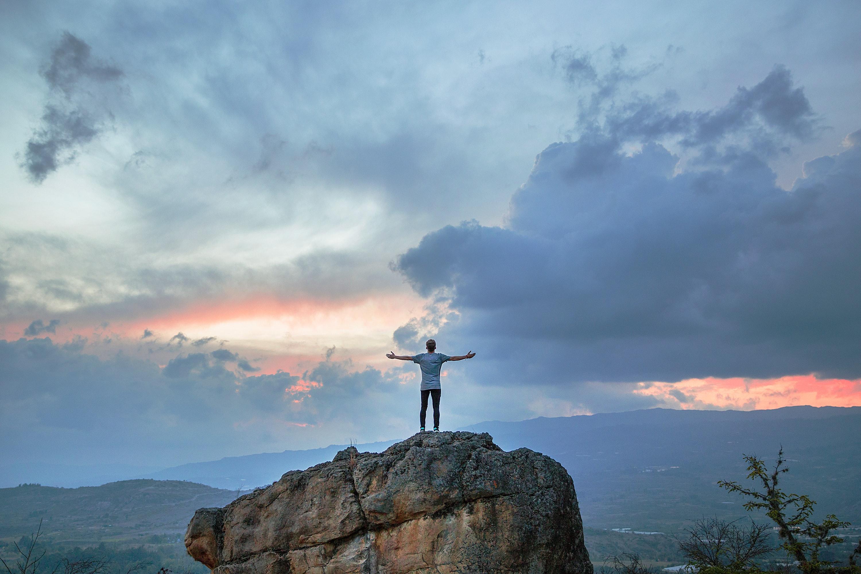 mies seisoo vuoren päällä kädet levitettyinä