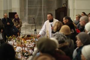 Varsovan Zbawicielan kirkossa siunataan pääsiäislauantaina kansalaisten Święconka-koreja, jotka sisältävät leipää, munia, piparjuurta, makkaraa, juustoa ja suolaa pääsiäisaamiaiselle. Kuva: Vesa Häkkinen